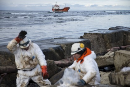 Members of the ECOSPAS clean up oil slicks on the coast, with the Russian tanker Nadezhda seen on the background, in the Far Eastern port city of Nevelsk